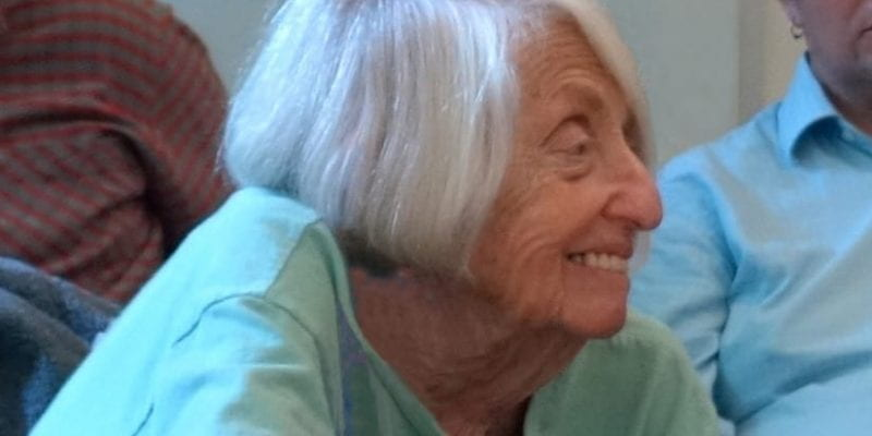 A cropped photo of Helene Moglen in profile, leaning forward and smiling while listening.