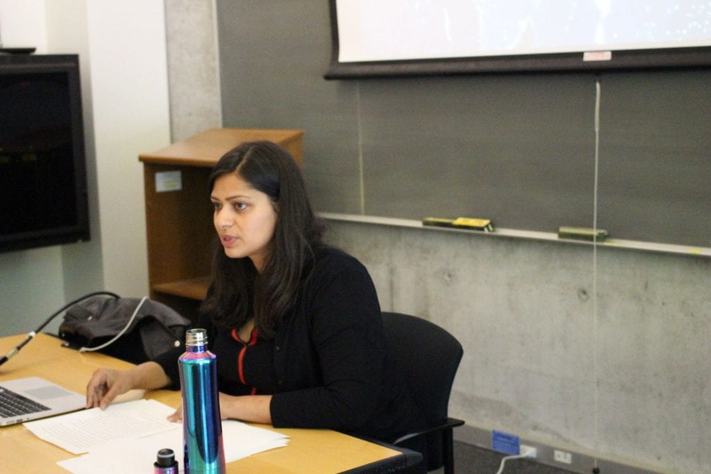 Dr. Nidhi Mahajan speaking while seated at a table