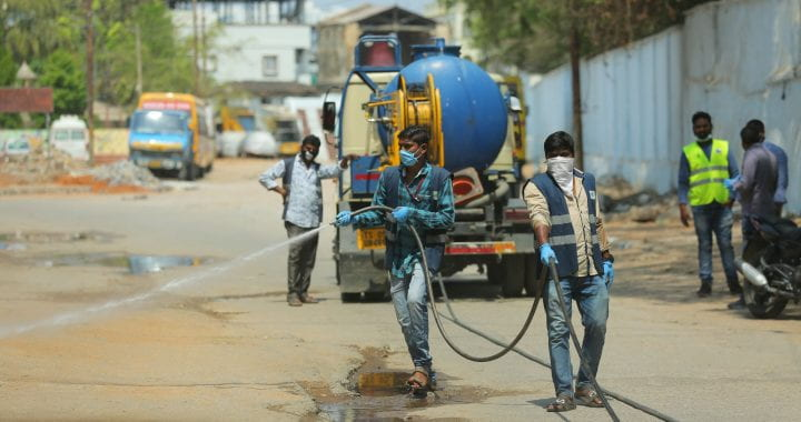 Photo of men in masks spraying a street in Hyderabad, India