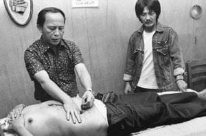 Photograph of Agpaoa placing his hands on the abdomen of a male patient.