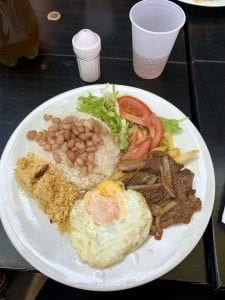 Brazilian lunch of beams, rice and fried eggs and flour.