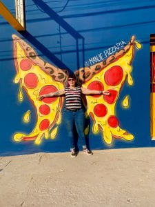 Jessy posed in front of street artwork of two slices of pizza resembling butterfly wings.