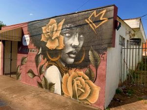 Street artwork on a building of an Afro-Latina woman with golden roses and a crown