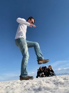 A man at the Salt flats lifting his foot in the air while a group poses in the background crouched down to make it seem he is stepping on them.