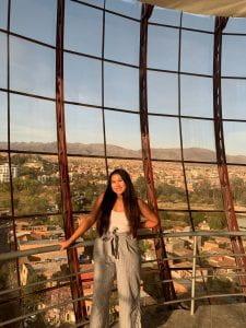 Adrianna standing in front of a wall of windows overlooking Tarija.