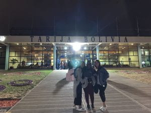 """Adrianna and friends posing in front of a sign that reads """"Tarija Bolivia"""" near the airport."""