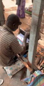 A man named Sam hand weaving a bag
