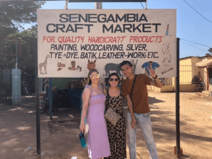 Alexis with two friends posing for a photo at the Senegambia craft market