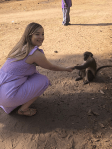 Alexis posing with a small monkey, they are shaking hands