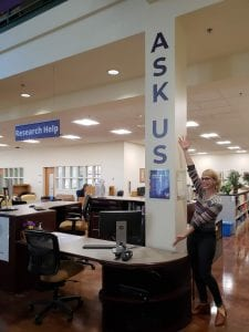 Image of desk in Snoqualmie Building, with Ask Us on the wall, a librarian, and the research help sign.