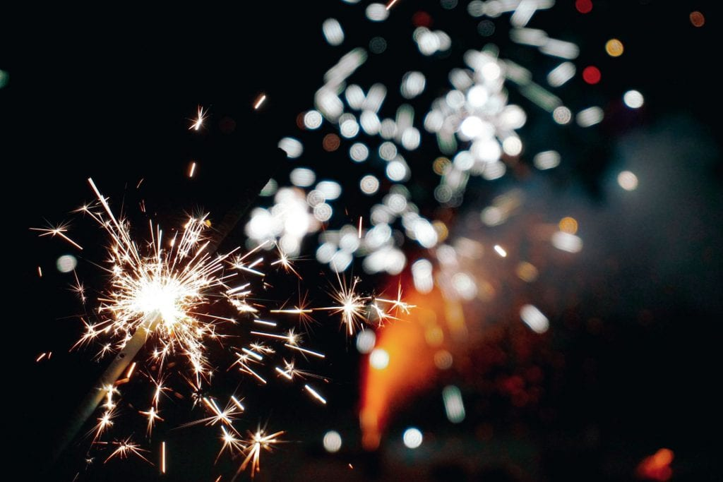 Image of a lit sparkler against a dark background. Bright, white sparks fill the frame.