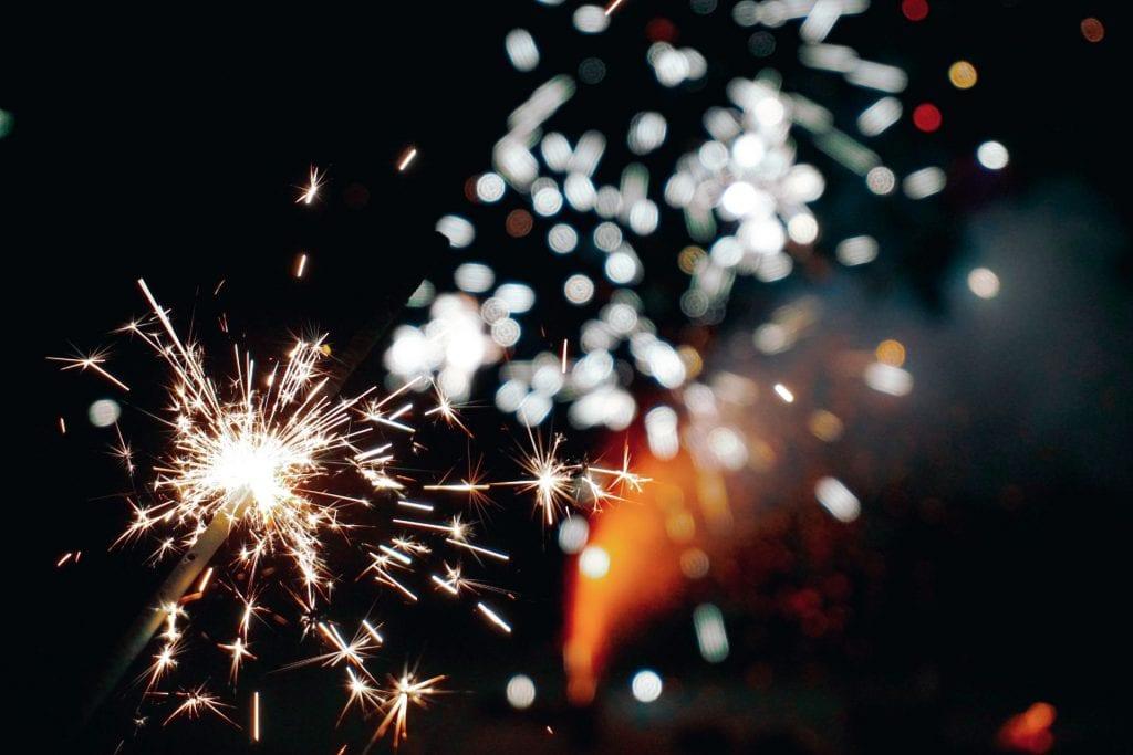 Image of a lit sparkler against a dark background. Bright, white sparks fill the frame.