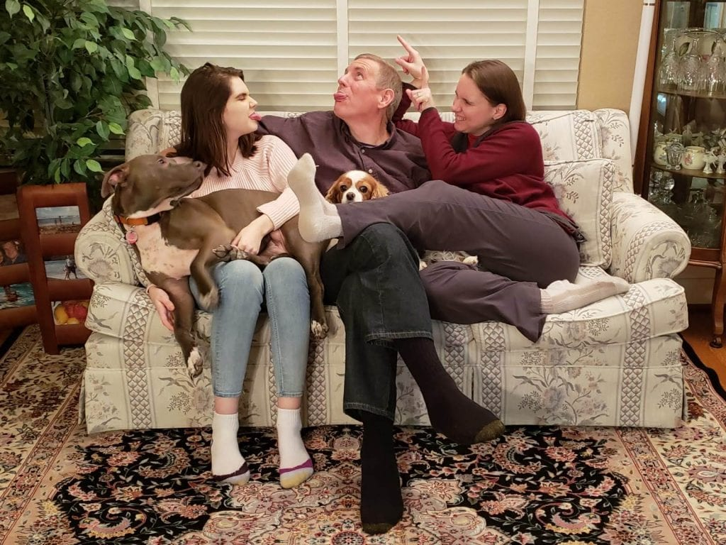 Picture of three people on a couch with a dog being silly.