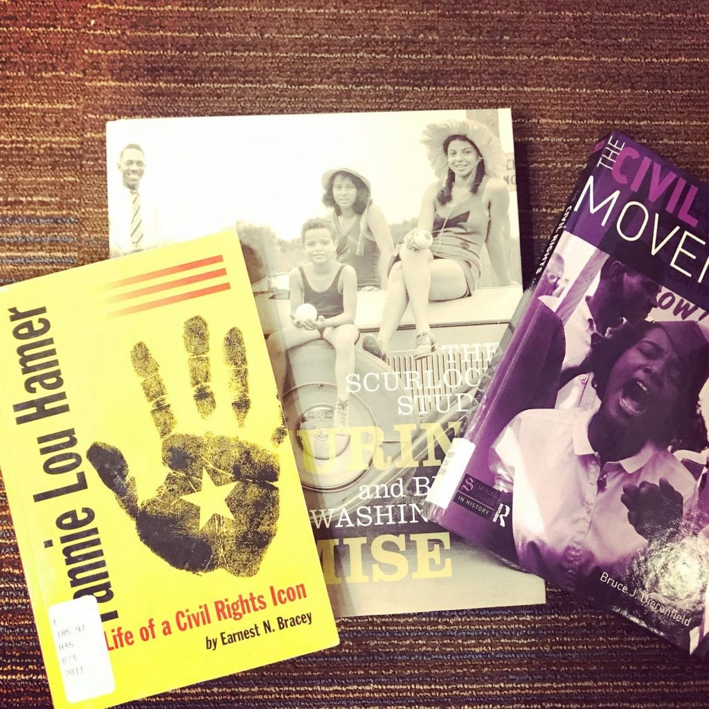 Pictures of three books on floor, all about civil rights