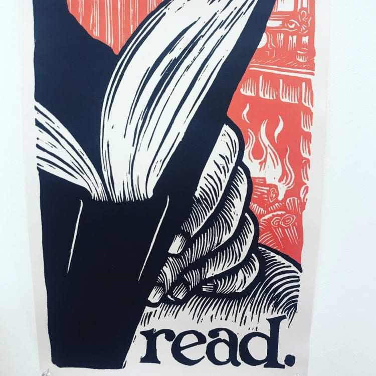 """Woodblock print of a book being read with the word """"read"""" below it. Colors are red, black and white."""