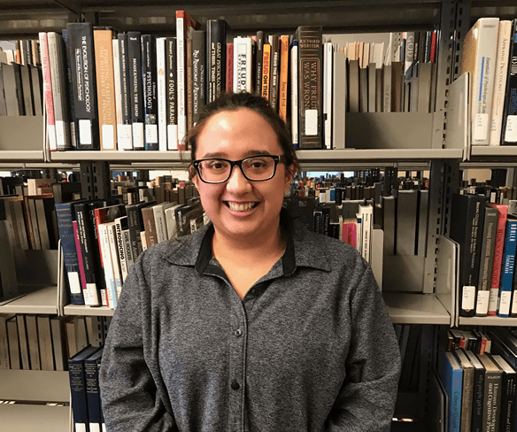 picture of young female library employee in front of book shelf