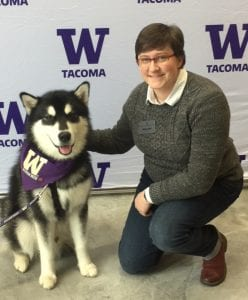 Photo of a woman with cropped hair crouched next to the UW Tacoma Mascot, Dubs II the Husky Dog!