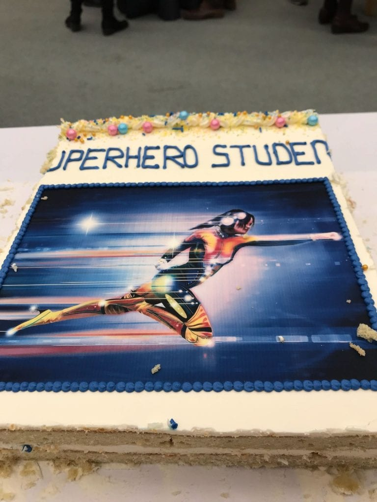 "photo of a sheet cake with ""superhero student"" written on top, and a picture of a female-bodied superhero"