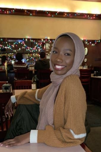 Image of a young woman of color with a headscarf, possibly in a restaurant)