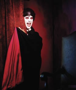 Image of a vampire appearing from behind a red velvet curtain