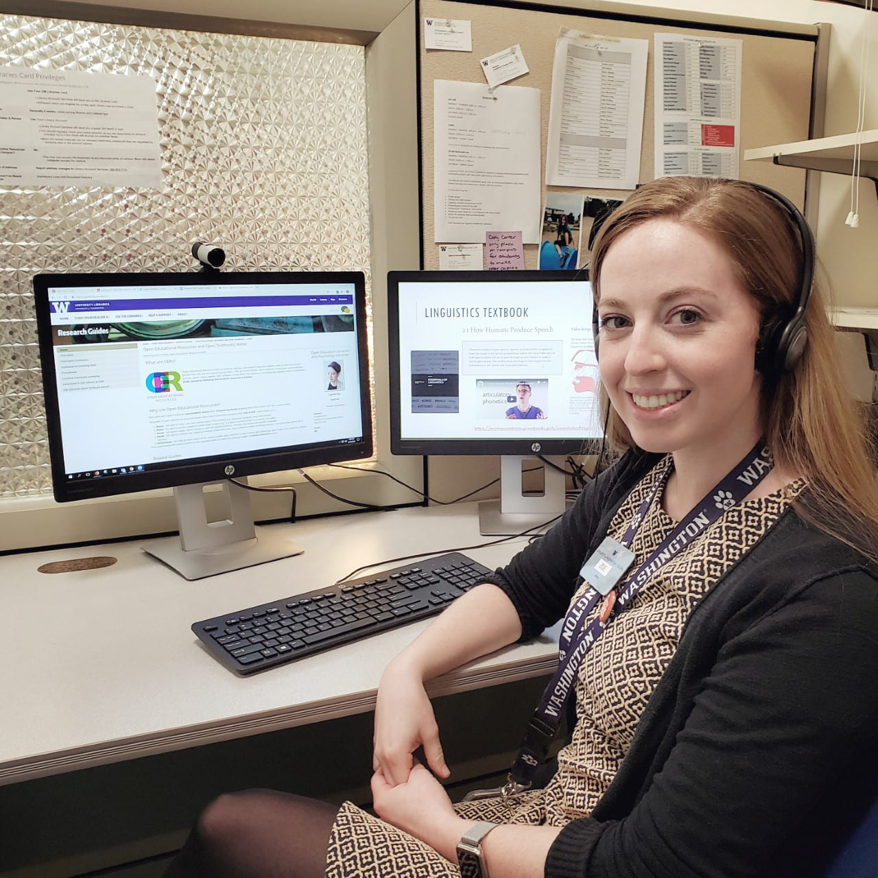 Woman smiling and sitting at her computer, while listening to online presentation about Pressbooks authoring platform.