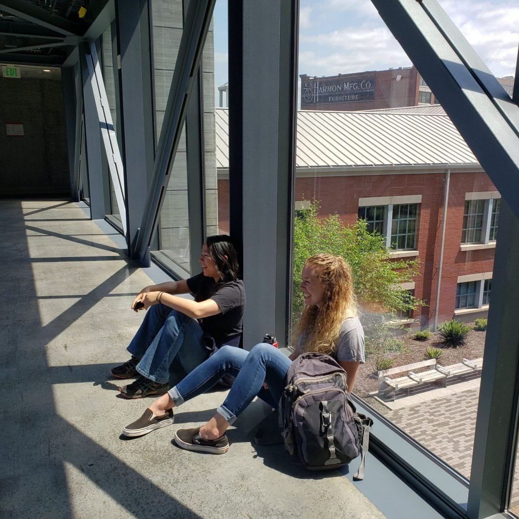 Two people sit with their backs against a glass wall a couple of stories above the ground behind them