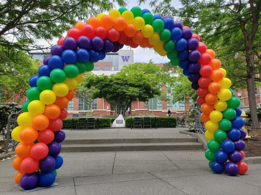"""An arch made of rainbow balloons frames the area in front of the Snoqualmie Building and the purple """"W"""" on the Tioga Library Building in the background"""