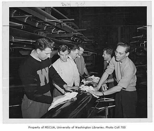 Black-and-white image of 6 people in a crew boat shed polishing the underside of a boat