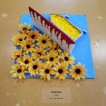 Yellow flowers, a bloody barrier, and yellow beads in a paper boat