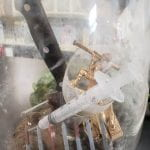 A syringe, knife, nails, and army toy in a dirty vase