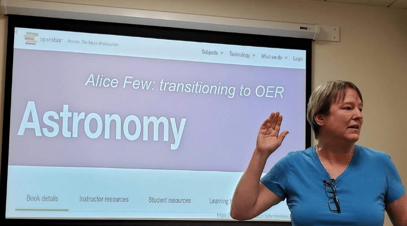 "A person raises their right hand while speaking in front of a screen with the title ""Alice Few: transitioning to OER: Astronomy"""