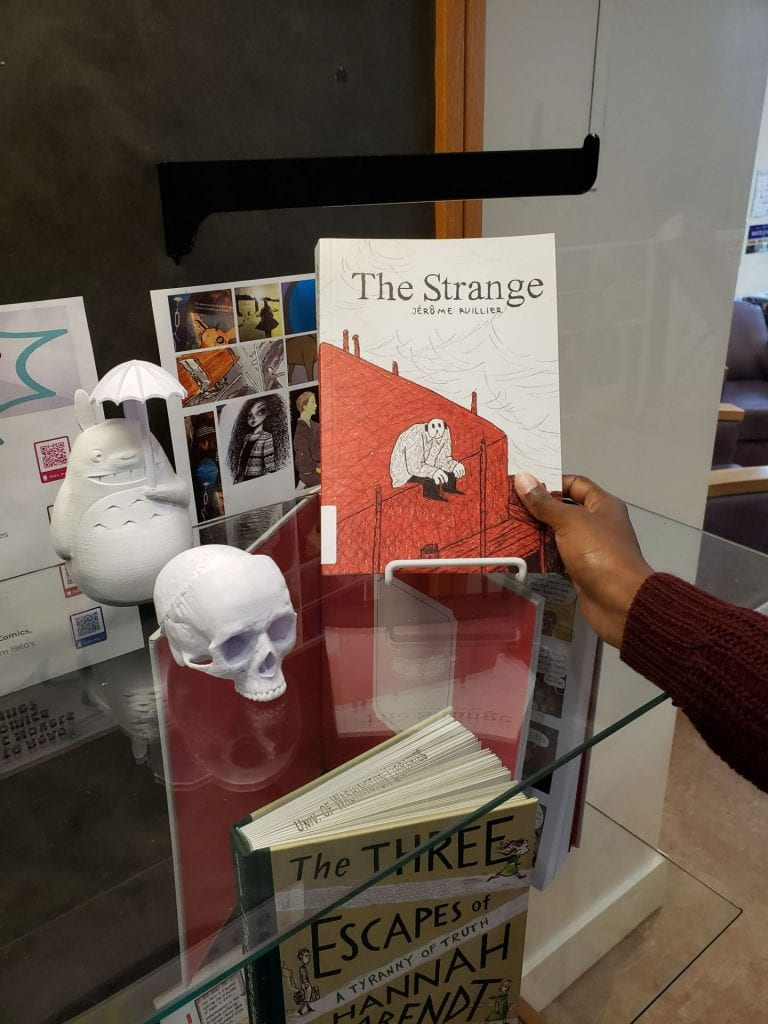 "Hand reaching in to grab ""The Strange"" by Jérôme Ruillier"