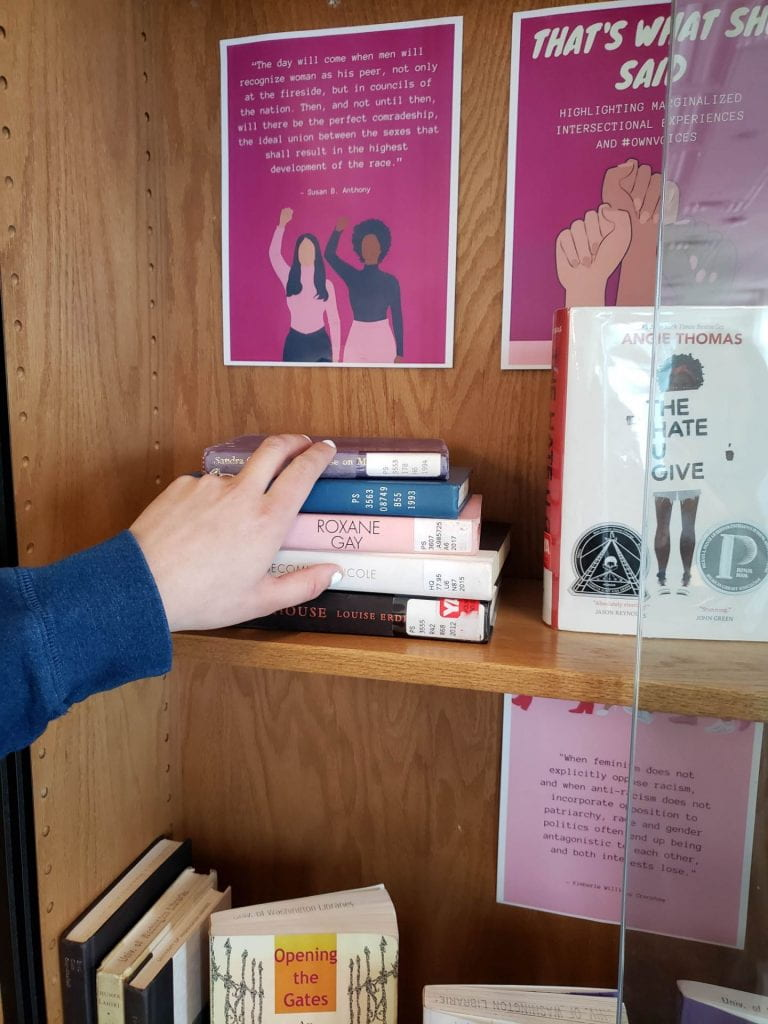 "Hand reaching to grab stack of books from ""That's What She Said"" display"