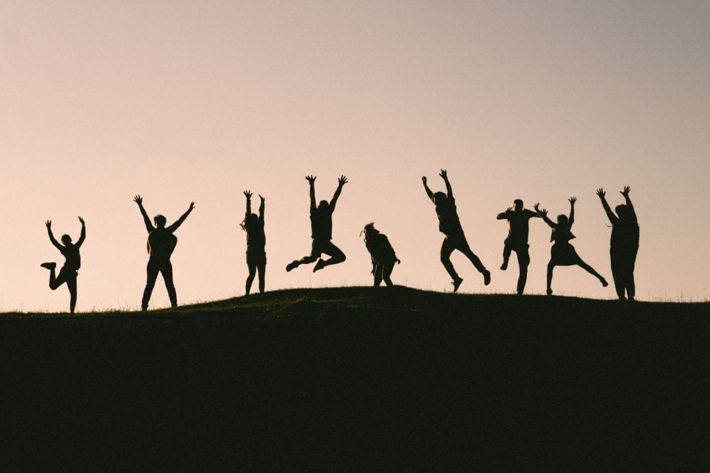 A row of people in silhouette, jumping for joy.