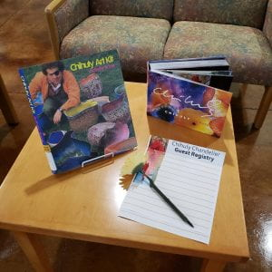 2 Chihuly books on a coffee table with a guest registry and pen
