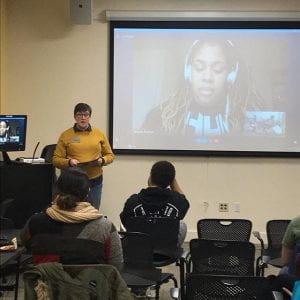 A person standing in front of a large projector screen where Angie Thomas is talking to the audience via Skype.
