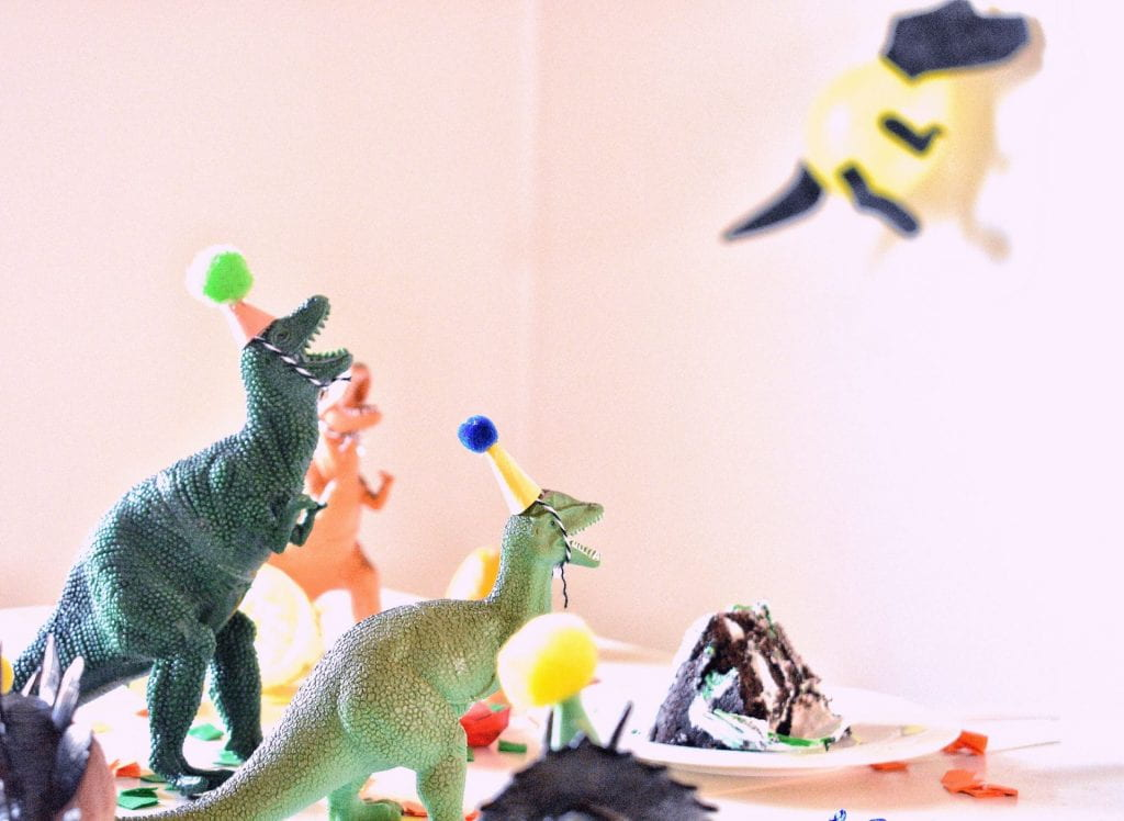 A group of toy dinosaurs wearing birthday party hats. In the background is a slice of cake.
