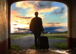 A silhouette of a person holding a suitcase, facing a sunrise.