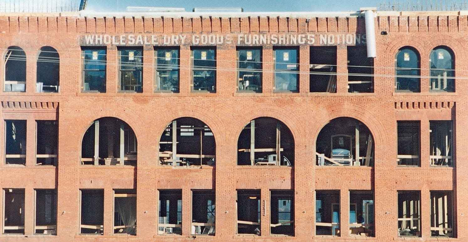 Image of facade of a brick warehouse building undergoing renovation.