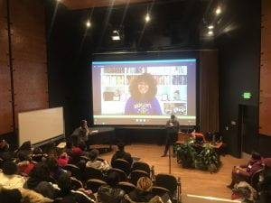 Image of Elizabeth Acevedo on a large screen in a University auditorium, participating in a skype call with students.
