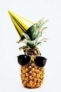 A pineapple against a white background. A pair of sunglasses and a party hat have been placed on the fruit, mimicking a face.