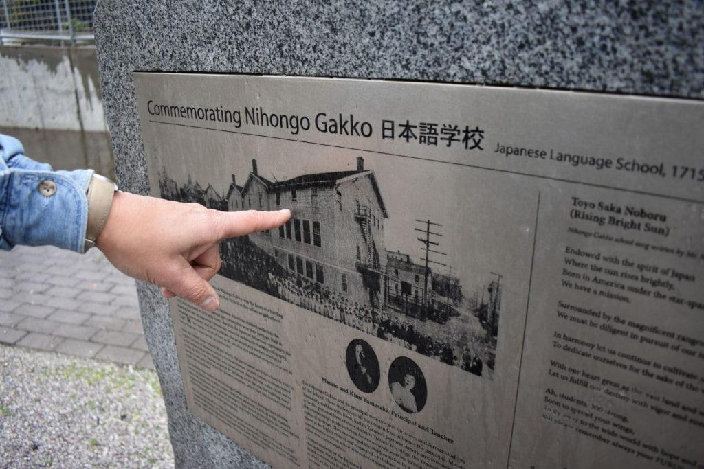 Greg Tanbara points at Japanese Language School memorial.