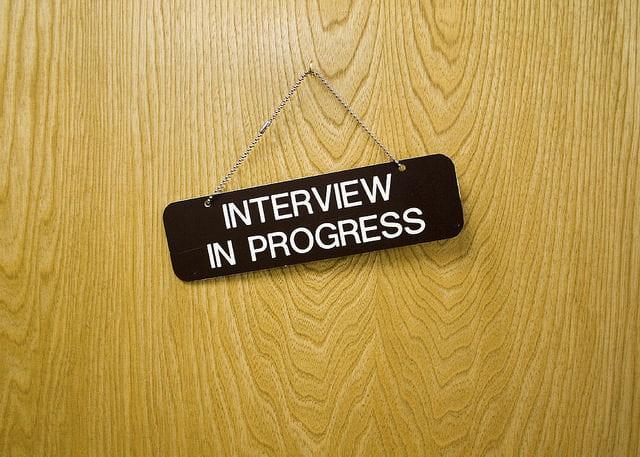 """A door sign saying """"interview in progress"""""""