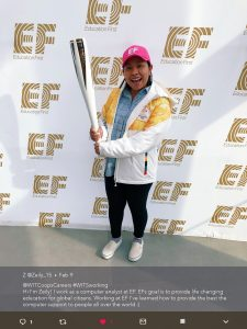 "Conest image submited of Zeily Perez holding olympic torch in front of ""EF Education First"" banner. Twitter camption included reads ""Hi I'm Zeily! I work as a computer analyst at EF. EFs goal is to provide life changing education for global citizens. Working at EF I've learned how to provide the best the computer support to people all over the world."""