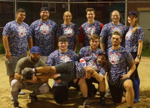 men and women pose on a softball field