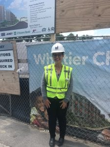Woman in construction vest and hardhat on site