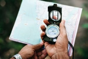 hands holding a compass and an open map