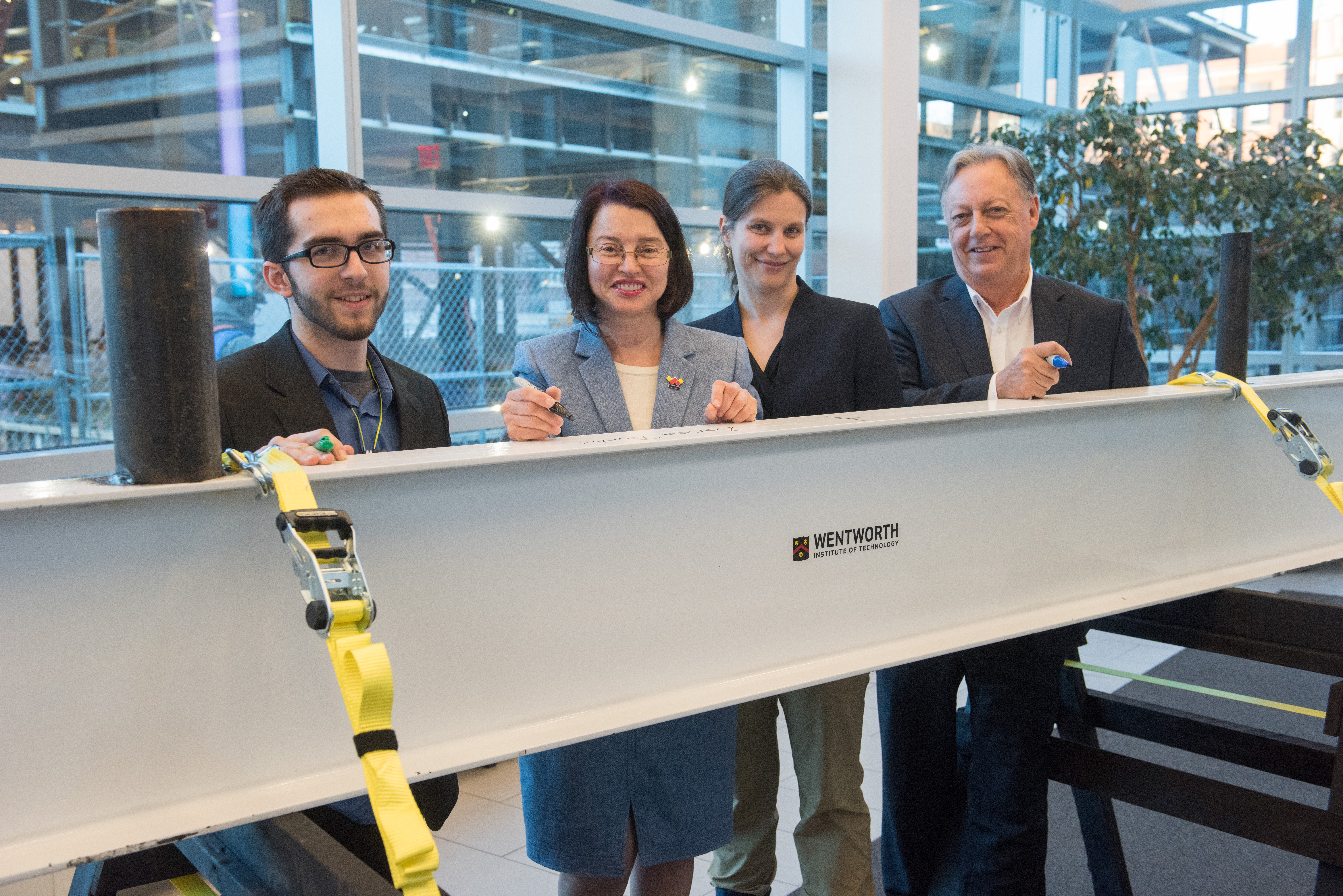 "Signature Moment: Wentworth Student Government President Chris Joanis, BSAM '18, Wentworth President Zorica Panti?, Faculty Senate President Emma Smith-Zbarsky, associate professor in the Applied Mathematics Department, and Eric Overström, senior vice president for academic affairs and provost, sign a structural beam to celebrate the ""topping off"" of the new academic building for engineering, innovation, and sciences in February."