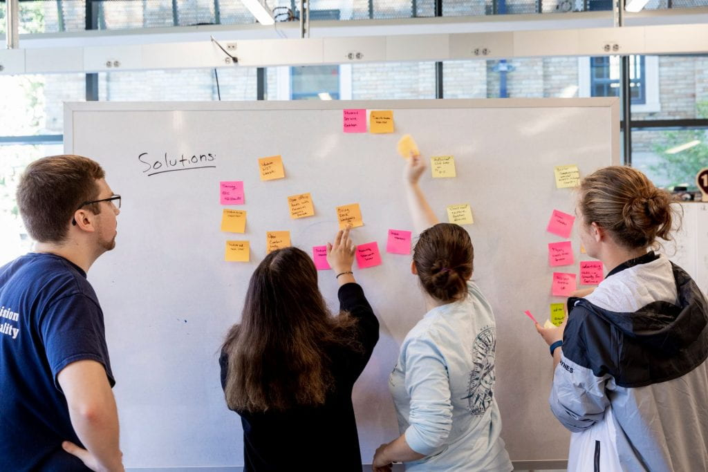 students placing sticky notes on a whiteboard