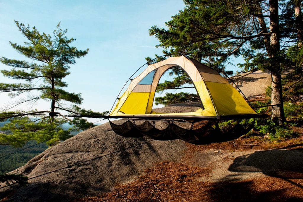 yellow tent perched on a mountain